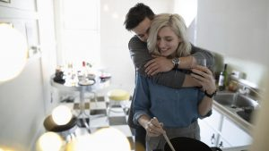gettyimages 1014367764 300x169 - Affectionate young couple hugging, cooking in apartment kitchen